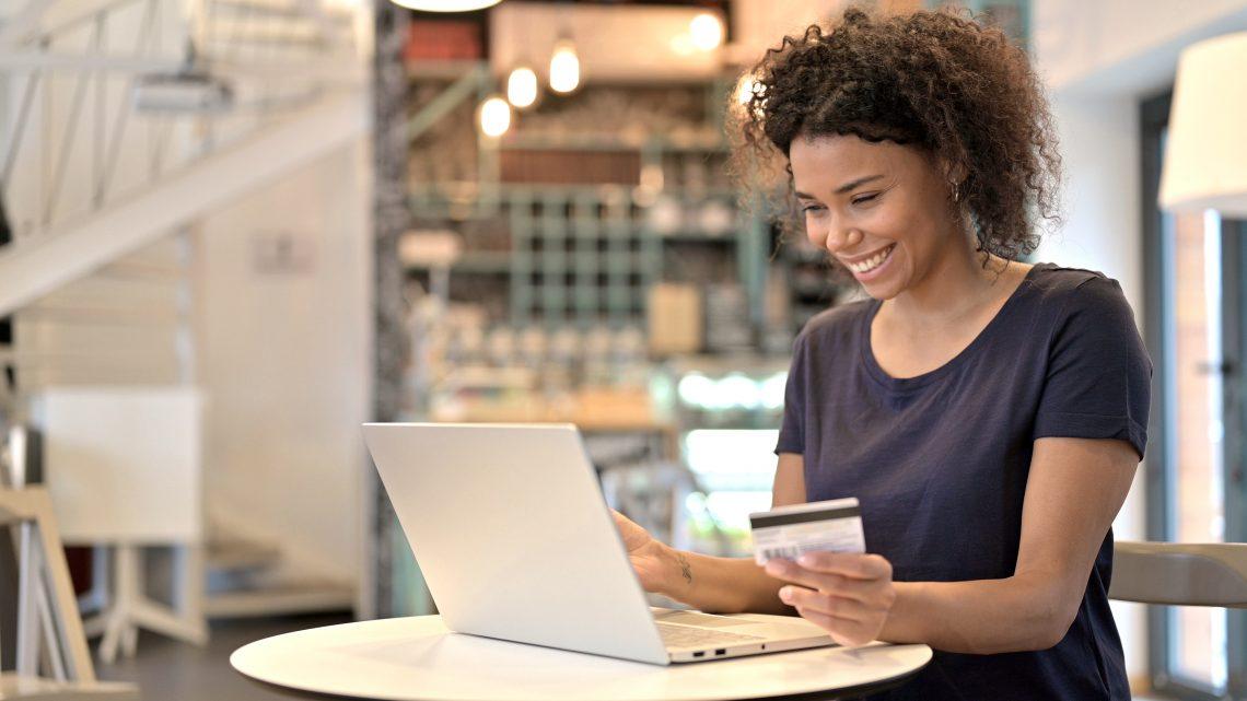 mulher mexendo no computador com um cartão de crédito na mão