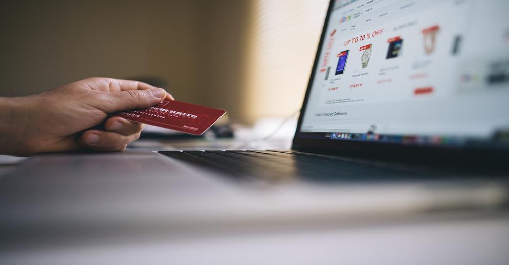 Imagem de uma mão segurando um cartão em frente a um computador representando roubos de dados